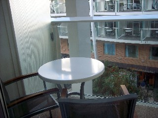 Photo of our Central Park balcony table and chairs overlooking the open-air core of the park.