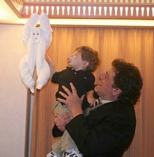 Photo of Joe holding Casey to touch a hanging towel animal goes here.